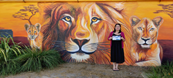Irma standing in front of a lion mural