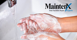 A pair of washing hands are covered in soap bubbles, ready to be put under a running faucet in a white sink basin.