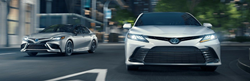 Silver and White 2021 Toyota Camry Models on a City Street
