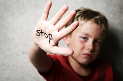 child being abused with his hand that says stop in black marker