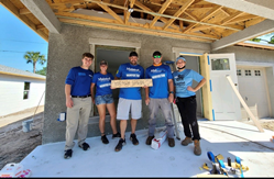 Five MaintenX team members all dressed in blue shirts pose outside the under-construction Horton home in Clearwater, FL.