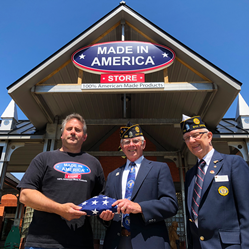Made In America Store Founder & CEO, Mark Andol, handing off a folded U.S.A. flag to veterans