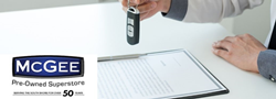 Man holding a vehicle key and contact below it accompanied by McGee pre-owned superstore logo
